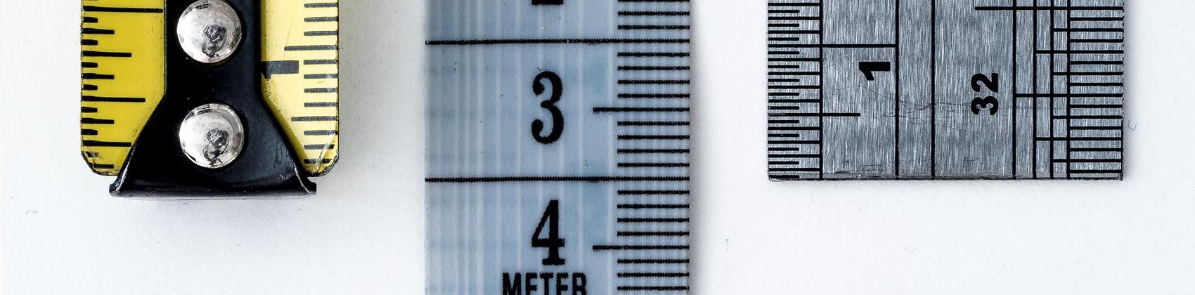 Close up van drie verschillende meetlinten en linealen